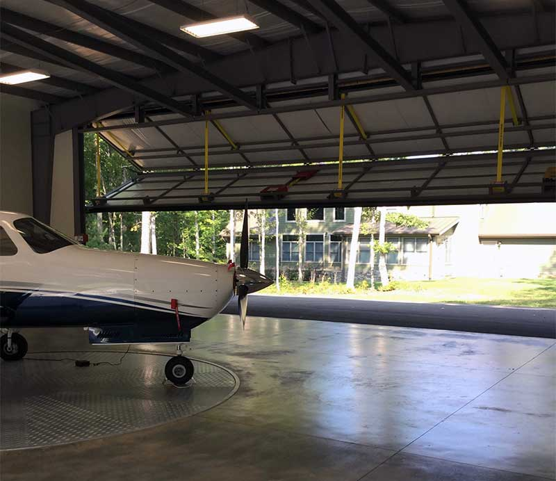 Two big 48 x 15-foot Schweiss bifold liftstrap/autolatch doors open on both ends of the hangar. The front of his Piper Malibu Matrix is shown on the remote controlled carousel that allows him to rotate the plane for easy exit.